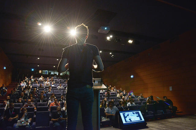 Orateur sur scène, vu de dos et à contre-jour, pendant les conférences Paris Web 2016