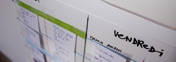 Photographie d'un planning en papier sur lequel sont posés de petits morceaux de papier agrémentés de titres de conférences.